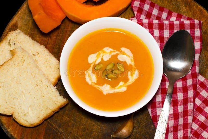 Kürbis- und Karottensuppe mit Sahne und Petersilie auf dunklem hölzernem Ba lizenzfreie stockbilder