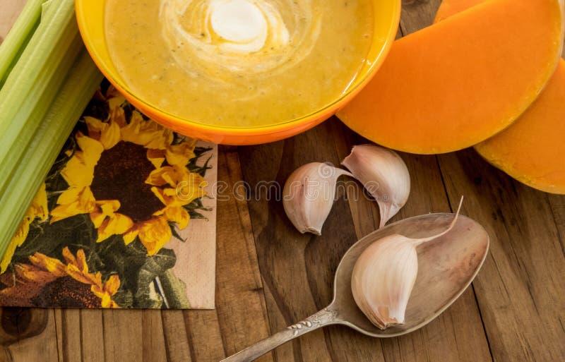 Kürbis- und Karottensuppe mit Sahne und Petersilie auf dunklem Holztisch mit selery, garlick und Stücken des Kürbises stockbild