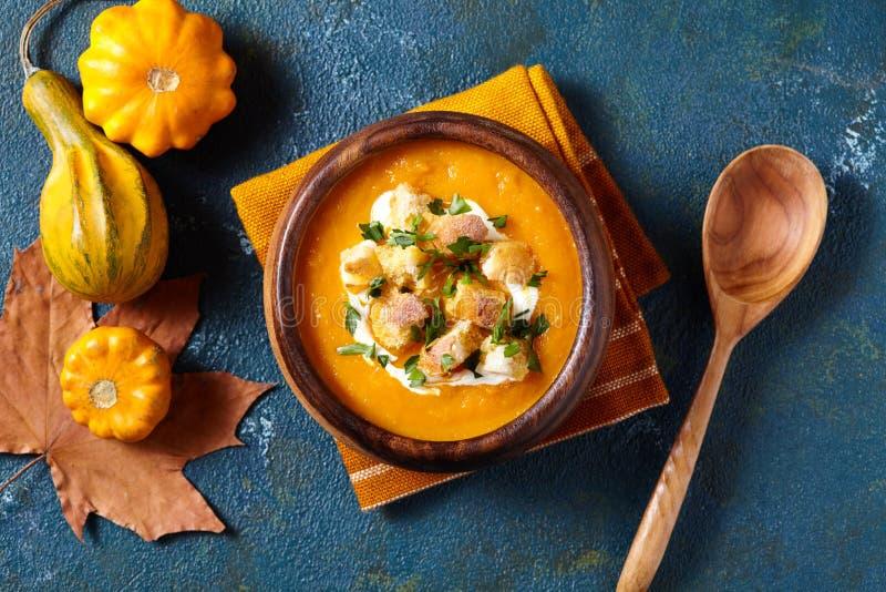Kürbis- und Karottensuppe mit Sahne, Petersilie, Croutons für Danksagung, Halloween Auf blauem kreativem Hintergrund Beschneidung lizenzfreies stockfoto
