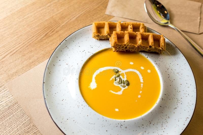 Kürbis- und Karottensuppencreme mit belgischen Waffeln auf hellem hölzernem Hintergrund Café, Restaurant oder Hausmannskost E lizenzfreies stockbild