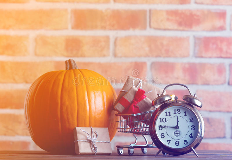 Kürbis und Wecker mit dem Warenkorb voll von den Geschenken stockbild