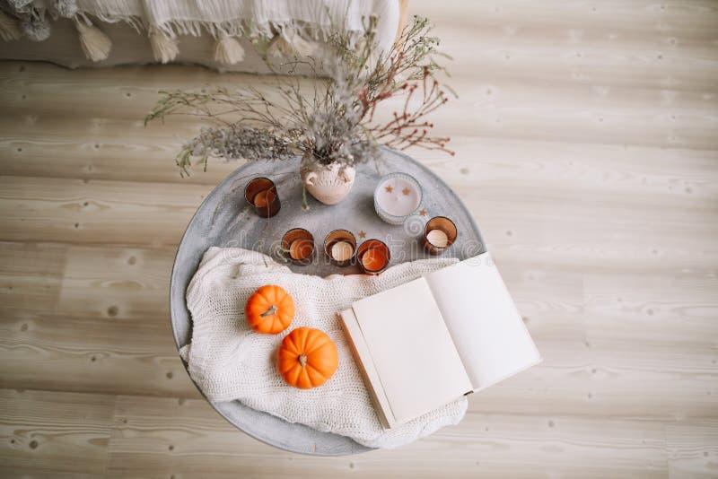 Kürbise, Kerzen, Buch und Trockenblumen mit warmer Decke Herbst, Fall, Halloween, Danksagungstageskonzept Flache Lage, Draufsicht lizenzfreie stockfotografie