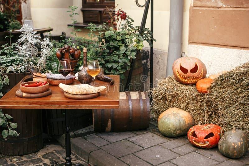 Kürbise mit furchtsamen Gesichtern auf Heu am Cafétisch, Feiertagsdekoration von Speicherfronten und Gebäuden Halloween-Straßende lizenzfreie stockfotos