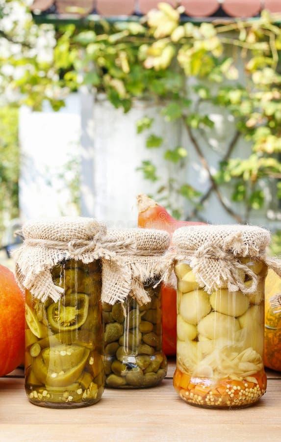 Kürbise und buntes in Essig eingelegtes Gemüse, wenn Glas konserviert wird stockfotografie