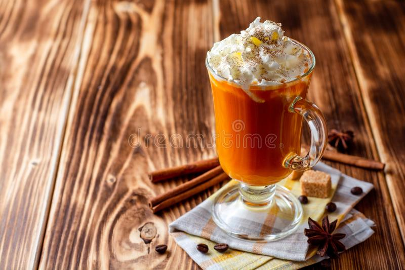 Kürbisgewürz Latte mit Schlagsahne und Zimt im Glas auf rustikalem hölzernem Hintergrund lizenzfreie stockbilder