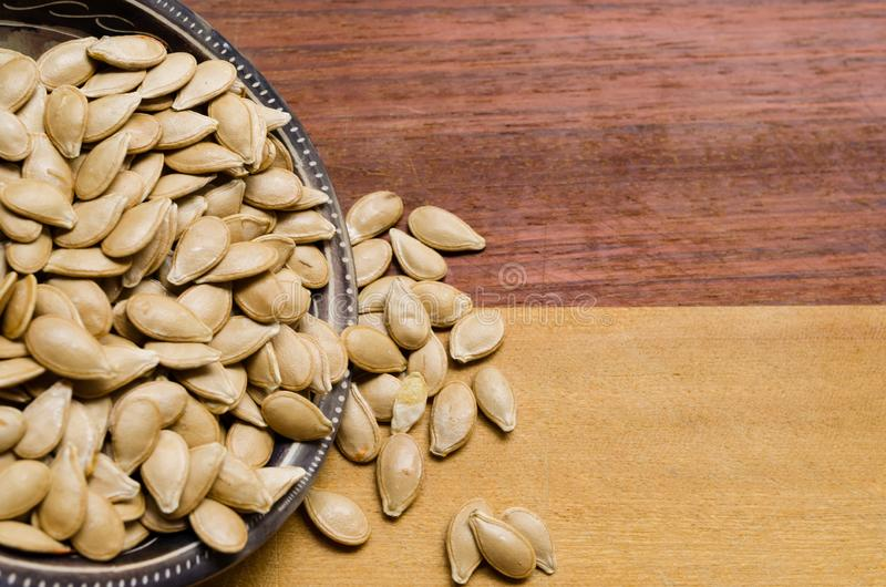 Kürbiskerne innerhalb einer kleinen Schüssel, mit einigen fallenden Samen, auf einer zwei-farbigen Holzoberfläche stockfoto