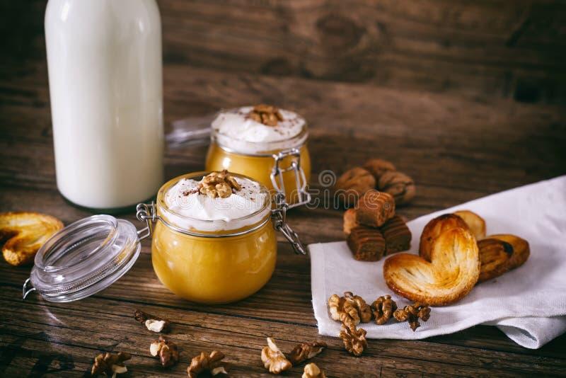 Kürbismilchshake im Glasgefäß mit Schlagsahne-, Toffee-, Walnuss- und Honigplätzchen Flasche Milch Dunkles hölzernes stockbilder