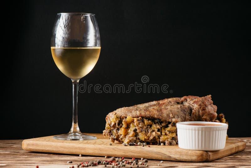 Kürbismuffin und gebackene Fleischroulade mit dem Füllen, zusammen mit einer Soße auf einer hölzernen Platte und einem Glas Weißw lizenzfreie stockfotografie