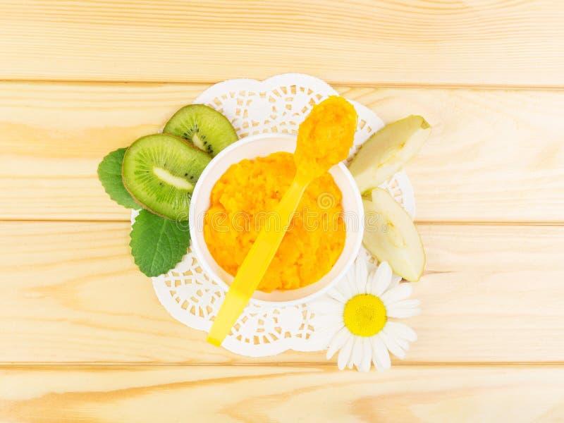 Kürbispüree, geschnittene Äpfel und Kiwi auf Hintergrundlichtholz lizenzfreie stockfotografie