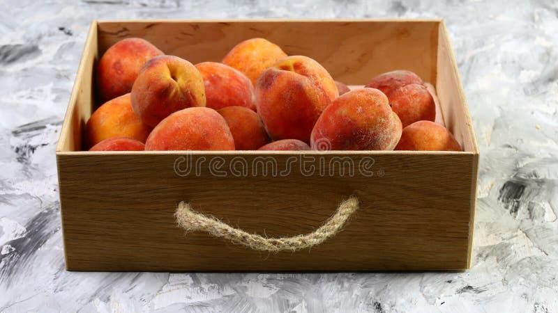 Kürzlich geerntete Pfirsiche in einem hölzernen Rahmen Auf der schwarzen Tabelle Freier Platz für Text Beschneidungspfad eingesch lizenzfreie stockbilder