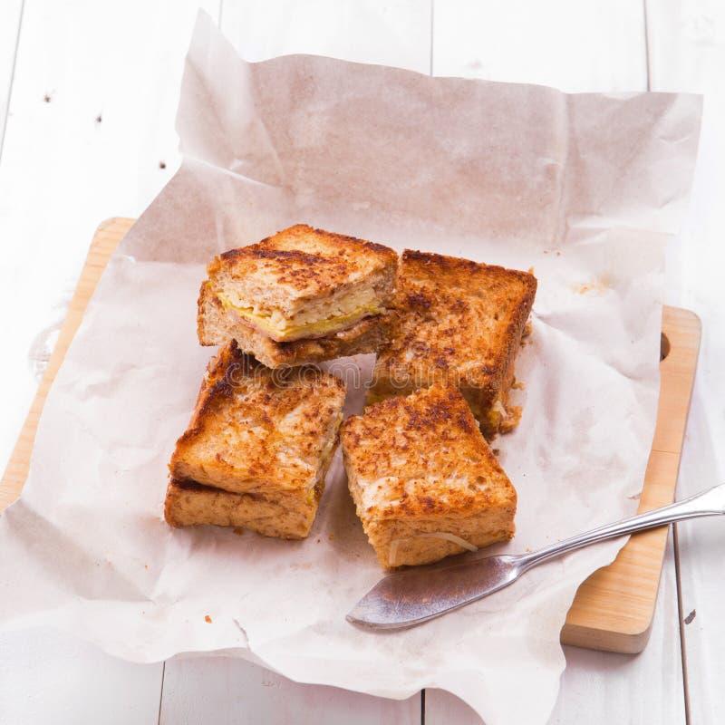 Kürzlich gemachte Club Sandwiche dienten auf einem hölzernen hackenden Brett stockbild