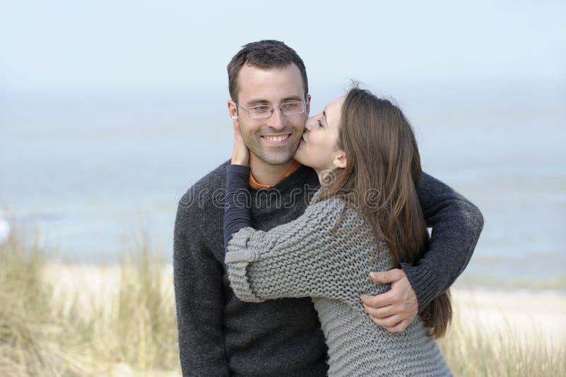 Küssen der jungen Paare am Strand stockbild