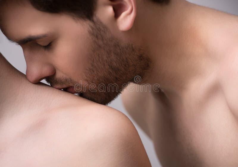 Küssen ihrer Schulter. Nahaufnahme von den hübschen jungen Männern, die seins küssen stockfotografie