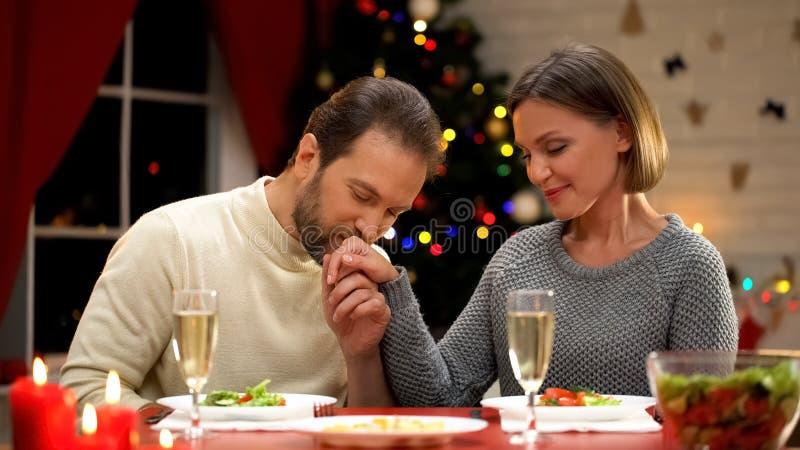 Küssende Damenhand des Mannes sorgfältig, romantisches Datum an Weihnachtsvorabend, liebevolles Paar habend lizenzfreies stockfoto