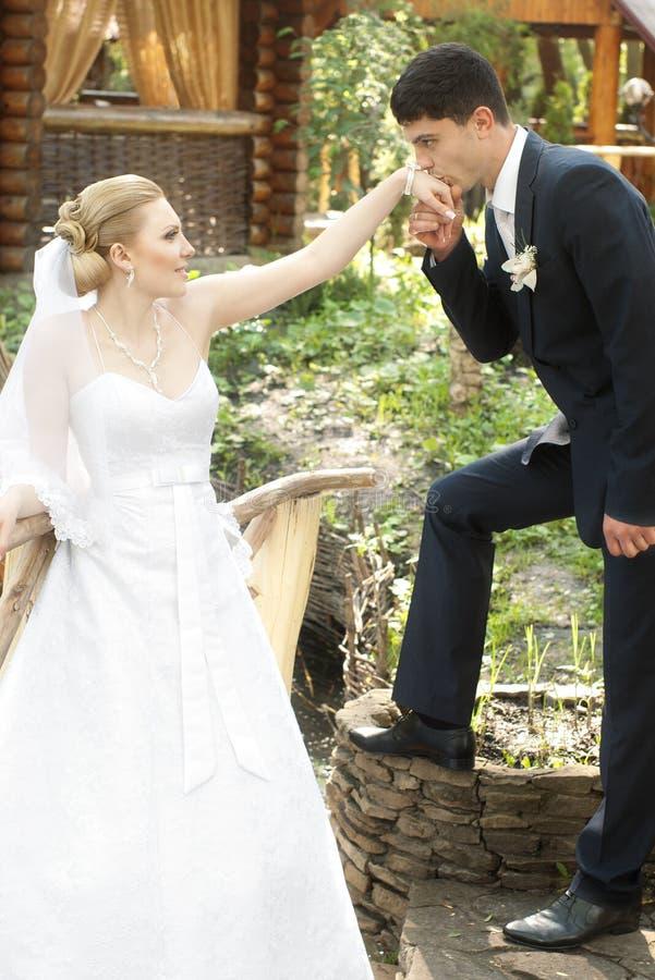 Küssende Hand des Bräutigams der Braut stockfotografie