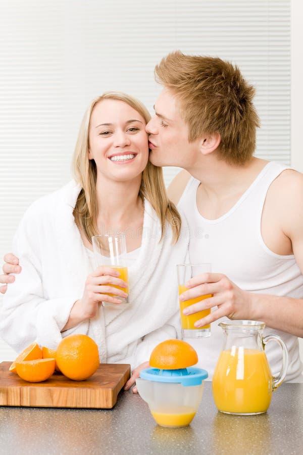 Küssende Paare des Frühstücks genießen Orangensaft lizenzfreies stockfoto