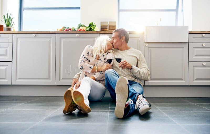 Küssender und trinkender Wein der älteren Paare in ihrer Küche lizenzfreie stockfotos