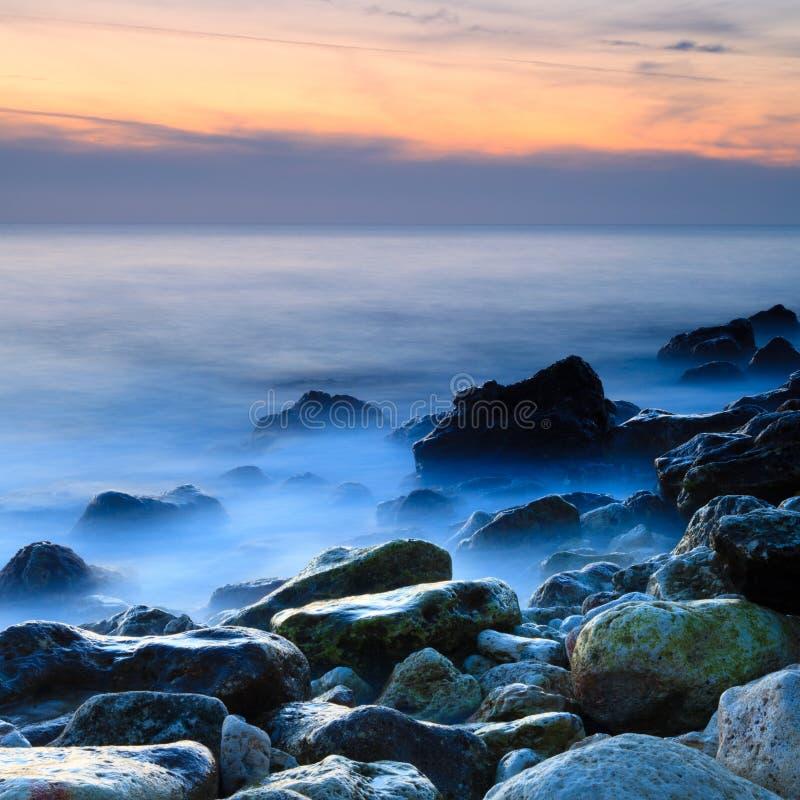 Küste mit nebelhaftem Wasser am Sonnenuntergang stockbilder