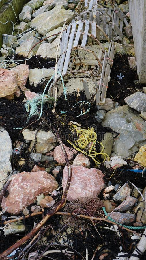 Küstenabfall angehäuft auf riprap stockbilder