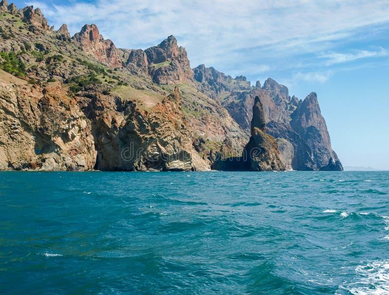 Küstenklippen des vulkanischen Ursprung auf Meer gegen Himmel stockfotografie