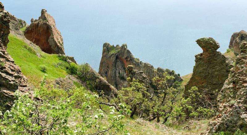 Küstenklippen des vulkanischen Ursprung gegen das Meer lizenzfreies stockbild