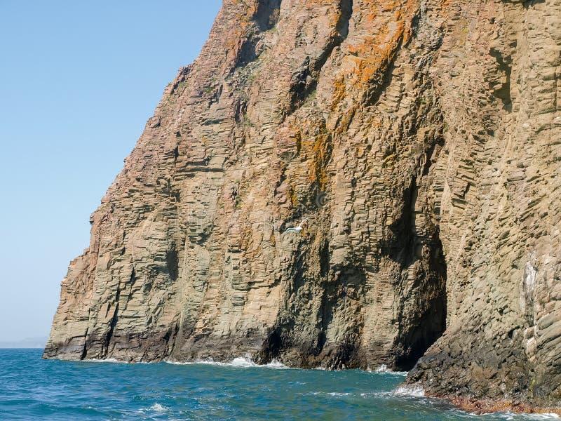 Küstenklippen des vulkanischen Ursprung gegen von von Meer und von Himmel lizenzfreies stockbild