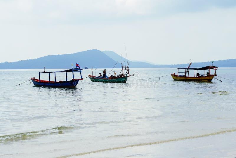 Küstenlandschaft mit kambodschanischen hölzernen Booten und entfernter Insel Idyllische Küstenansicht mit traditionellen Khmerboo stockbild