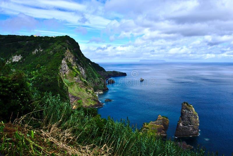 Küstenlinie auf Flores-Insel mit Corvo-Insel im Hintergrund Azoren Portugal lizenzfreie stockfotografie