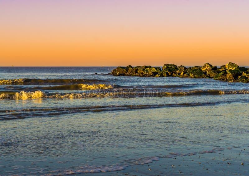 Küstenlinie des Strandes mit brechenden Wellen und des bunten Himmels während des Sonnenuntergangs lizenzfreie stockfotos