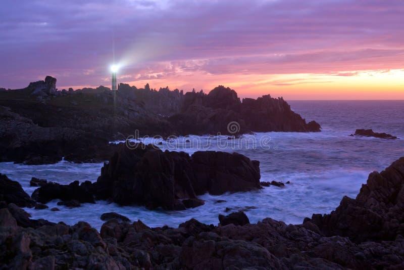 Küstenlinie und Leuchtturm an der Dämmerung stockfotos