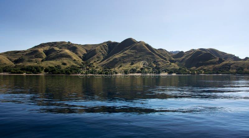 Küstenlinie von Bergen mit grüner Vegetation reflektierte sich im blauen Ozeanwasser in Flores, Indonesien stockfotos