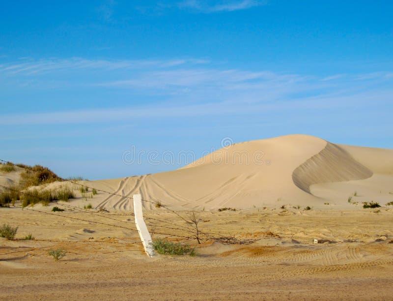 Küstensanddünen mit Reifenbahnen und Stacheldrahtzaun gegen blauen Himmel in Libyen stockfotografie