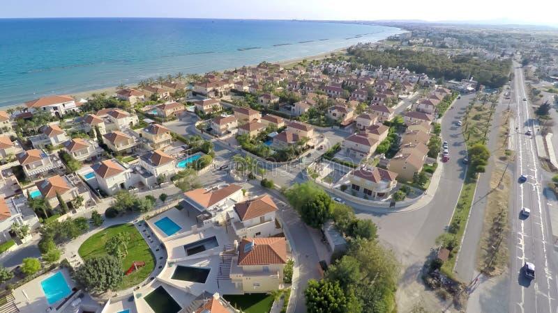 Küstenurlaubsstadt, atemberaubende Vogelperspektive von Luxushäuschen entlang Küstenlinie stockbilder
