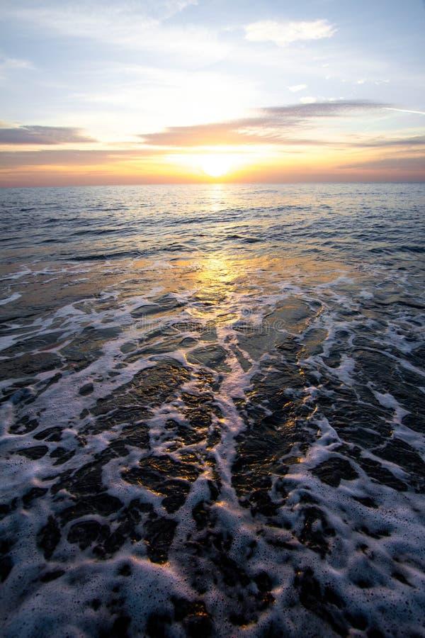Küstenwellen bei Sonnenuntergang Bunter Sonnenuntergang auf einem Seestrand lizenzfreies stockfoto