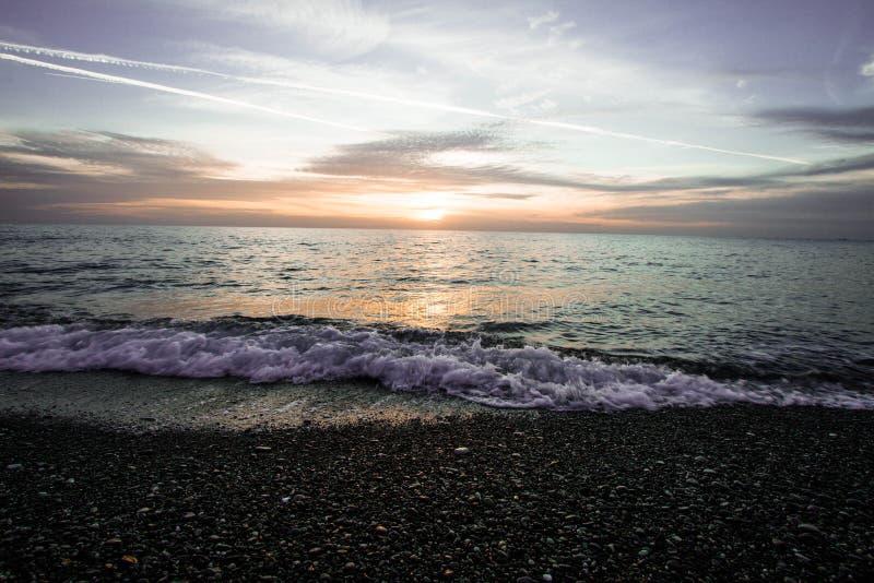 Küstenwellen bei Sonnenuntergang Bunter Sonnenuntergang auf einem Seestrand stockbilder