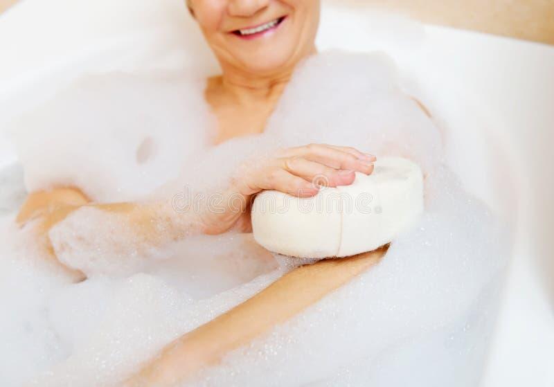 Kąpanie kobieta relaksuje z gąbką obrazy stock