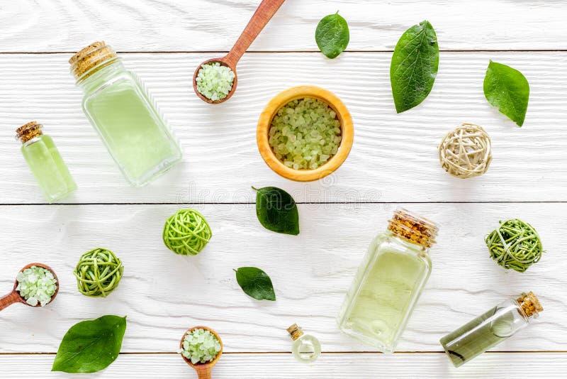 Kąpielowa sól w ziołowy kosmetycznym ustawiającym z herbacianą oliwką opuszcza na białym drewnianym tło odgórnego widoku wzorze obrazy royalty free