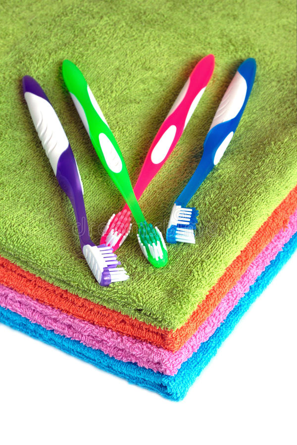 Kąpielowi ręczniki różni kolory i toothbrushes odizolowywający obraz stock