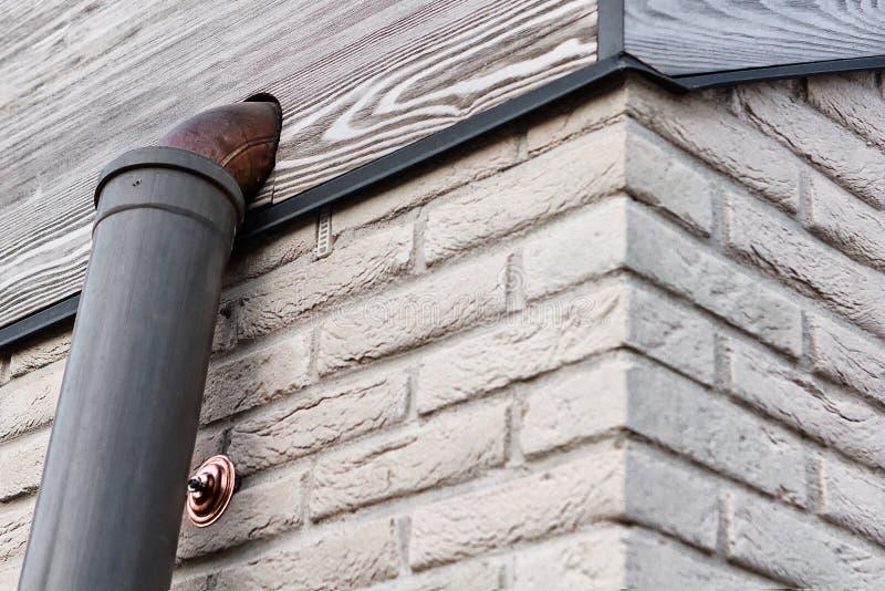 Kąt biała ściana z cegieł z szarą drewnianą antepedium deską i groszak drymba podczas budowy zdjęcie stock