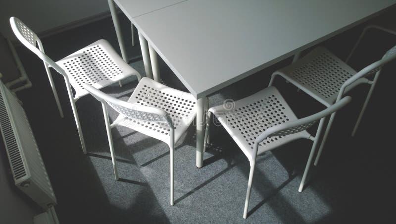 Kąt wielki biały konferencyjny stół i cztery krzesła obok on Zamknięty okno i grzejnik Pojęcie biznes fotografia stock