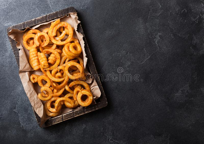 Kędzierzawa dłoniaka fasta food przekąska w drewnianym pudełku na kamiennym kuchennym tle Niezdrowy szybkie żarcie zdjęcia stock