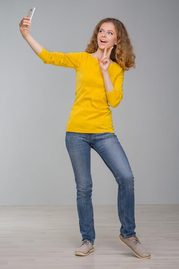 Kędzierzawa młoda kobieta w kolorów żółtych ubraniach joyfully z uśmiechem ma i zdjęcie stock