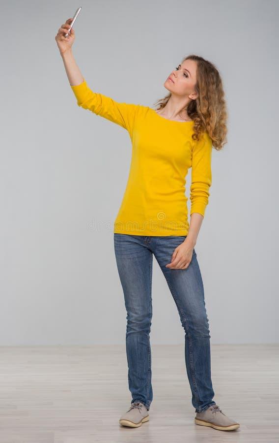 Kędzierzawa młoda kobieta w kolorów żółtych ubraniach joyfully z uśmiechem ma i zdjęcie royalty free