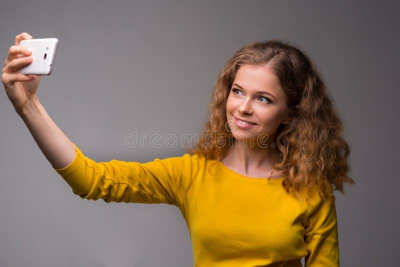 Kędzierzawa młoda kobieta w kolorów żółtych ubraniach joyfully z uśmiechem ma i fotografia royalty free