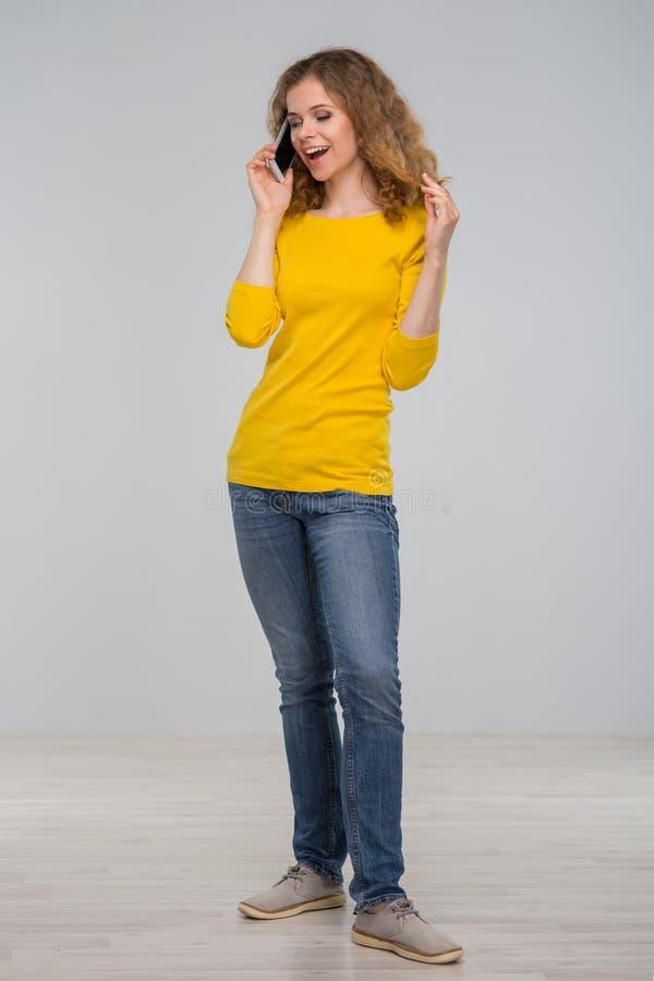 Kędzierzawa młoda kobieta w kolorów żółtych ubraniach joyfully z uśmiechem ta i zdjęcie stock