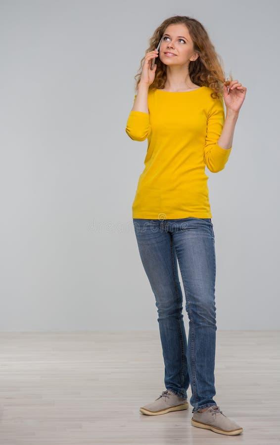 Kędzierzawa młoda kobieta w kolorów żółtych ubraniach joyfully z uśmiechem ta i obrazy royalty free