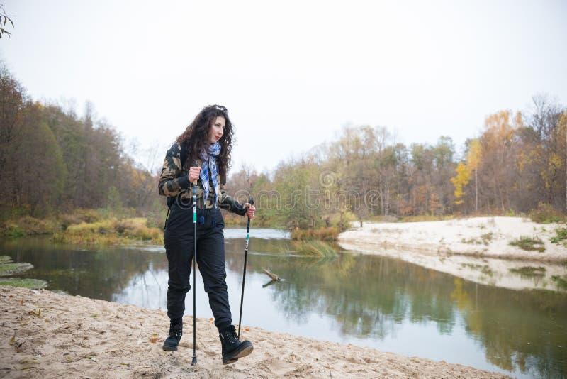 Kędzierzawa młodej kobiety dziewczyna pozuje przed jeziorem w lasowy Wycieczkować obraz royalty free