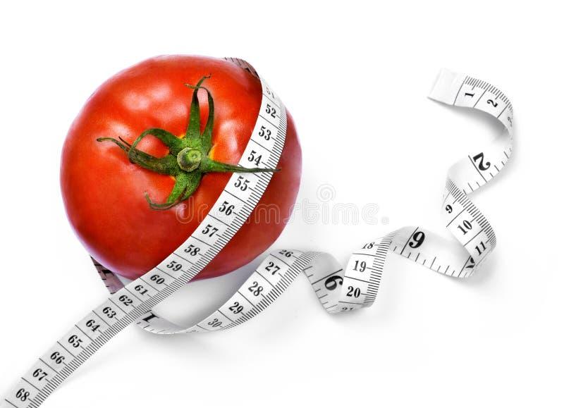 Kędzierzawa miara taśmy i pomidor obrazy royalty free
