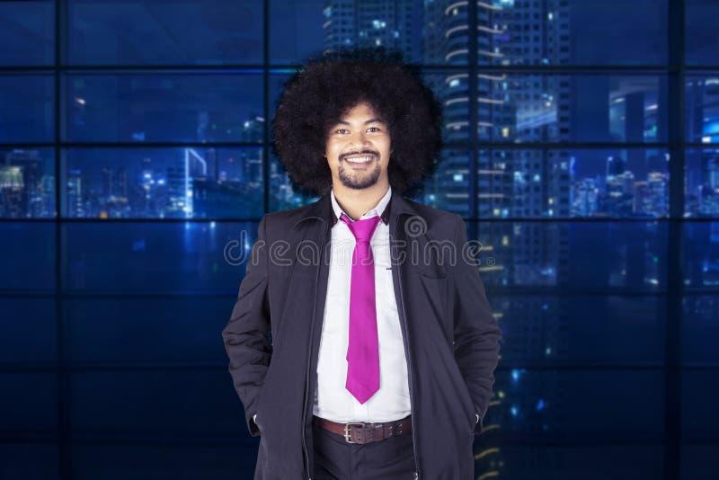 Kędzierzawego włosy biznesmena pozycja w biurze obraz stock
