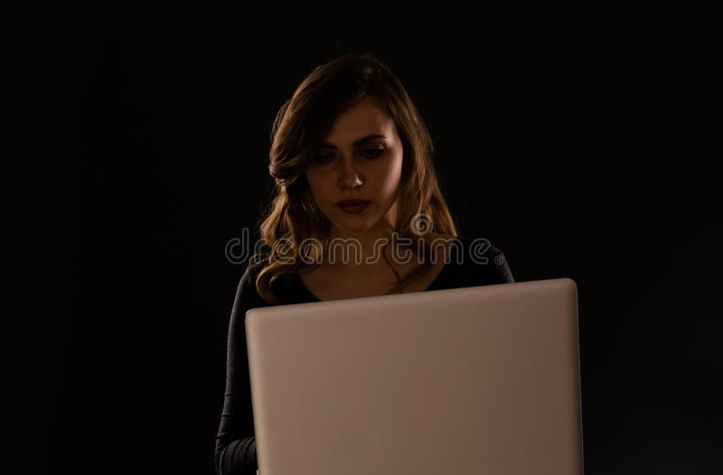 Kędzierzawego włosy dama używa laptop odizolowywającego nad ciemnym tłem obraz royalty free